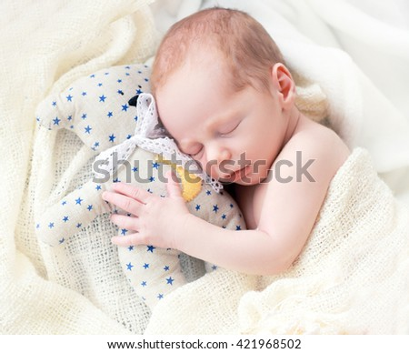 Baby sleeping with her teddy bear. New born relax in a white bedroom. Family at home. Love, trust and tenderness concept. Bedding and textile for nursery. - stock photo