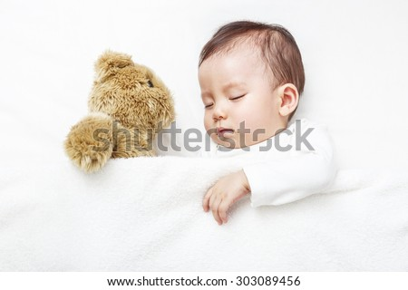 Baby sleepping with her teddy bear, new family and love concept. - stock photo