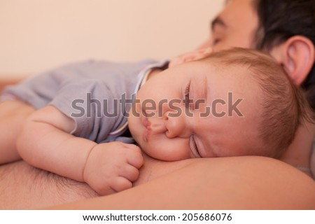 Baby sleeps on dad - tender care of his father - stock photo