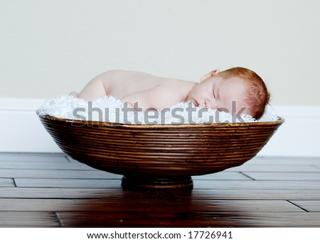 Baby sleeps on his belly in a fabric lined basket. Horizontally framed photo