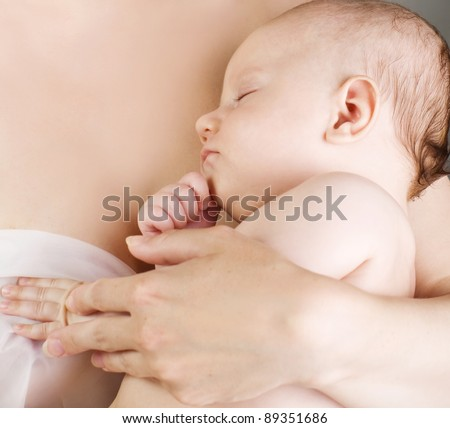 baby sleeps on mother's arms - stock photo
