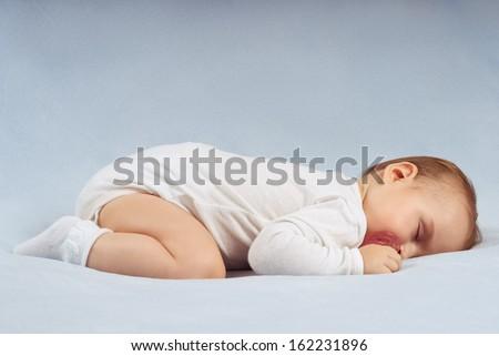 Baby sleeps on soft blue blanket - stock photo