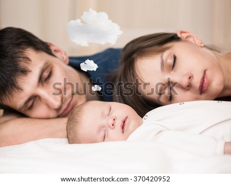Baby sleeps  with tired parents - stock photo