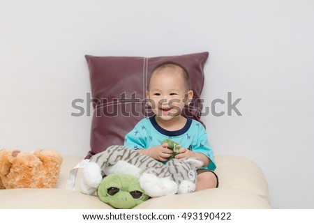 Baby smile sitting and play doll on the sofa.
