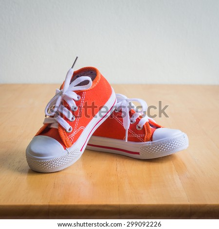 Baby sneakers on wooden table over wall grunge background, vintage style
