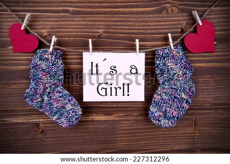 Baby Sockets and red Heart Hanging on a Line together with a Label on which stands It's a Girl - stock photo
