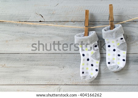 Baby socks hanging on clothesline on wooden background - stock photo