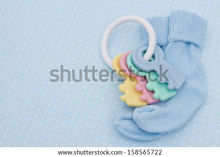 Baby soother and socks on a blue polka dots background with copy space for you message, Blue Baby Background - stock photo