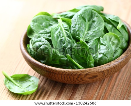 Baby spinach on a wooden background