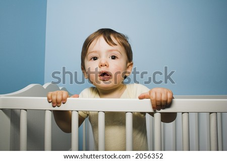 baby standing in his crib over blue wall - stock photo
