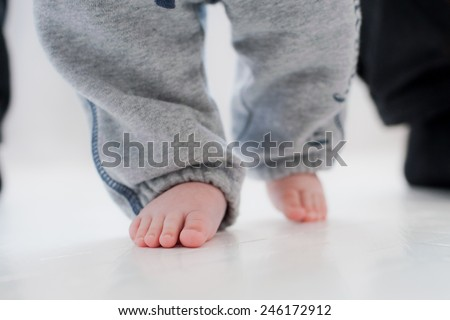 baby steps with the help of his father - stock photo