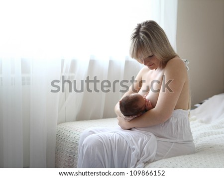 Baby sucking milk from mother's breast - stock photo