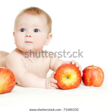 baby surrounded by red apples