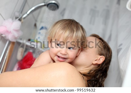 Baby taking a shower with mama - stock photo