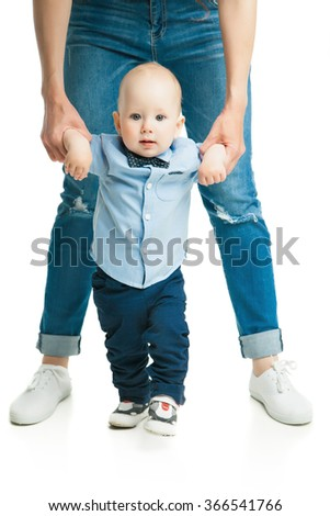 baby taking first steps with mother help  - stock photo