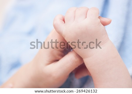 Baby taking his mother's hand