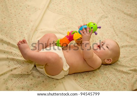 Baby teaching colors and shapes with multicolored rattle - stock photo
