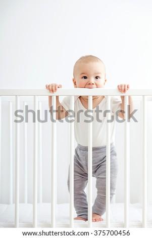 Baby teething and biting his crib. - stock photo