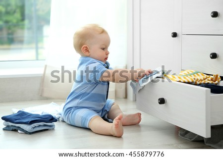 Baby throwing up clothes from wooden chest