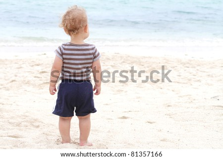 Baby, toddler boy on a tropical beach, looking at ocean