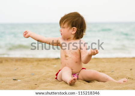baby toddler child girl playing on the sand beach takes sunbathe - stock photo