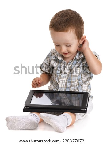 Baby toddler holding a digital tablet on his lap scratching his head in bewilderment, isolated on white - stock photo