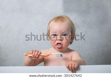 baby toddler learning to brush their teeth with a brush