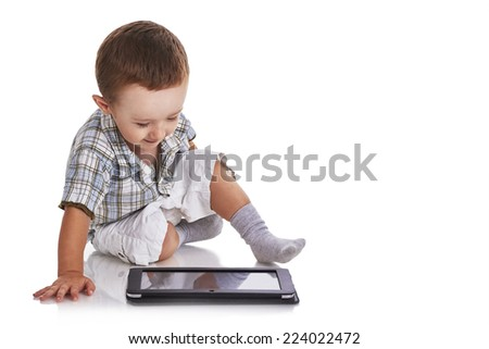 Baby toddler looking happy at a digital tablet on the floor, isolated on white - stock photo