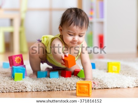baby toddler playing  wooden toys at home or nursery - stock photo