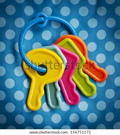 Baby toy keys over a polka dot background - stock photo