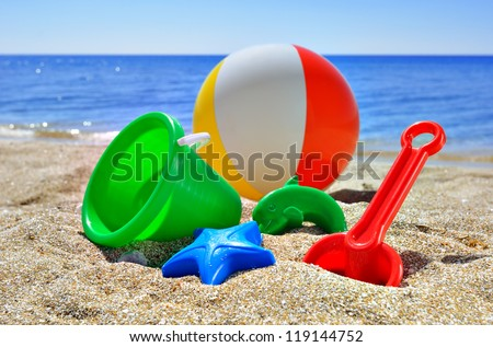 Baby toys on the beach sand against the blue sea and sky - stock photo