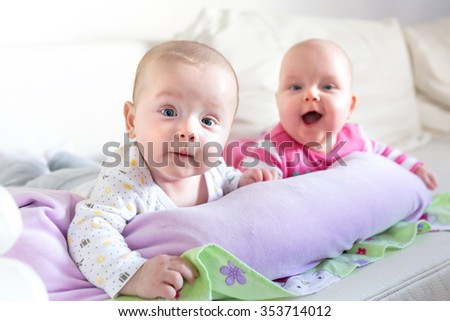Baby twins lie on his tummy - stock photo