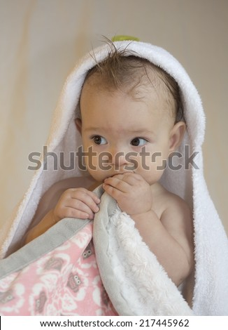 baby under white hooded towel holding blanket, against neutral background. Looking to left of camera. - stock photo