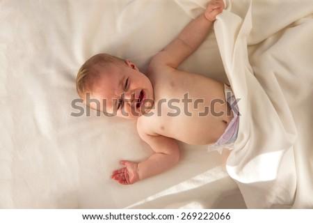 Baby upset lying in her cot - stock photo