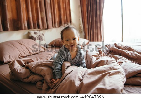 Baby wakes up in the morning in the bedroom - stock photo