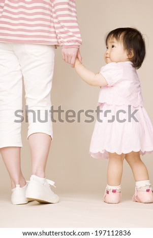 Baby Walking And Holding Hands With Mother - stock photo