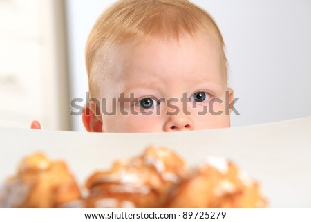 baby wants cake on the table - stock photo