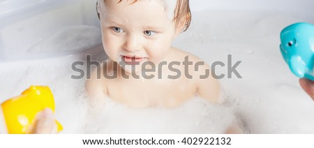 Baby wash in the bath. Playing with water toys. Use soap, shampoo for children. Baby shampoo not sting eyes
