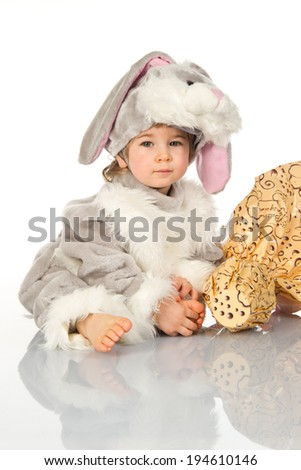 Baby wearing easter bunny costume with easter egg in yellow wrapping.