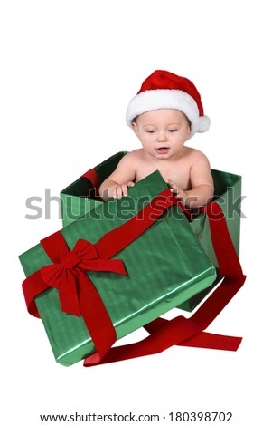 Baby wearing santa hat in Christmas present box with bow on white background  - stock photo