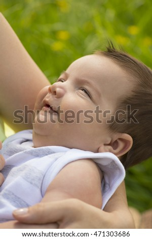 Baby (6 weeks) smiles in mother's arms, sideways, outdoors