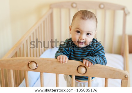 Baby with a cute happy face standing in a cot. - stock photo