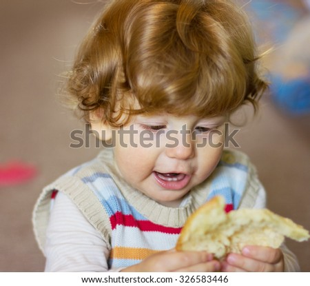 baby with a piece of bread in his hands. Little boy touching the bread. The child smelling a bread