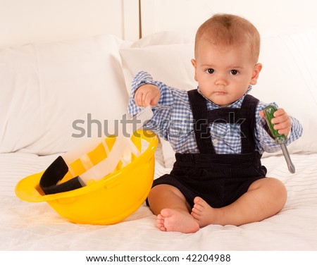 Baby with a safety helmet and a toy screwdriver - stock photo