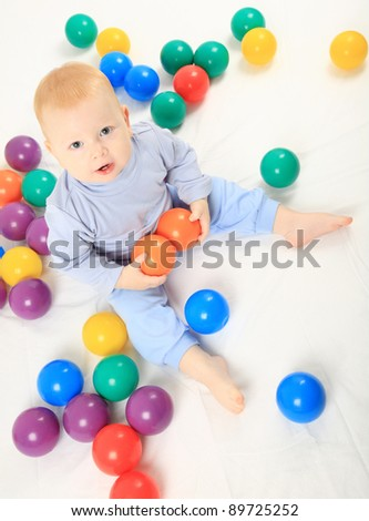 baby with balls on the bed - stock photo