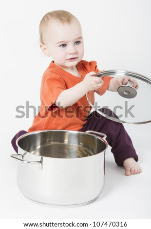 baby with big cooking pot on neutral background