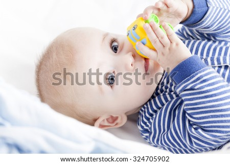 Baby with blue eyes playing with a toy - stock photo
