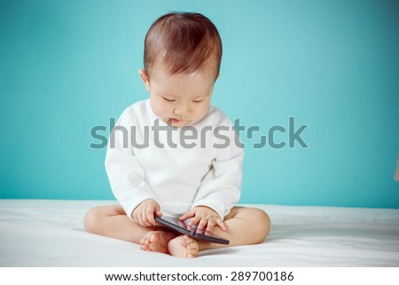 Baby with cell phone - stock photo