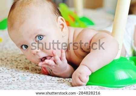 baby with finger in mouth near the toys - stock photo