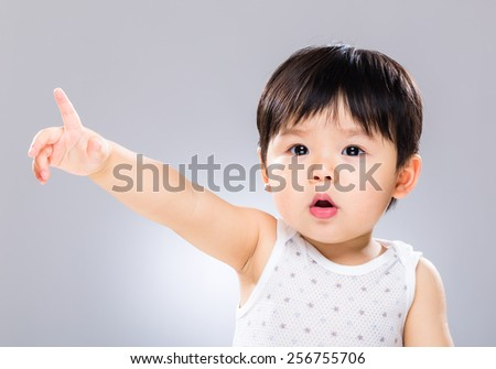 Baby with finger point to front - stock photo